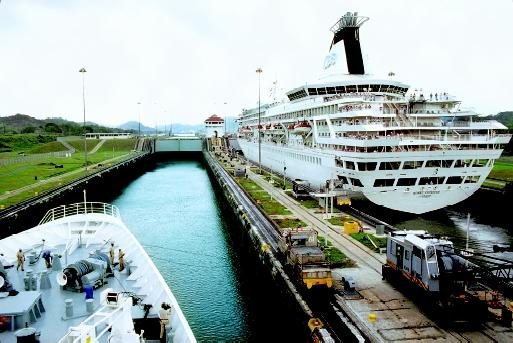 "A large cruise ship and another oceangoing vessel pass through the Miraflores Locks of the Panama Canal. This large navigation canal, connecting the Pacific and Atlantic Oceans, is often referred to as the ""eighth wonder of the world."""
