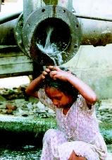 A girl in Dhaka, Bangladesh bathes in water leaking from a giant pipe on March 22, 2000, which ironically was designated World Water Day. Inadequate water supply in this city of 9 million has forced many residents to drink and bathe from derelict surface-water sources.