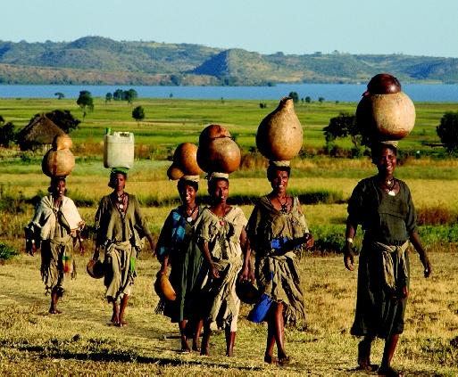 Women in Ethiopia carry water from a lake (in background) back to their homes. The time spent hauling water can be significant in areas where sources of domestic water supply are limited.