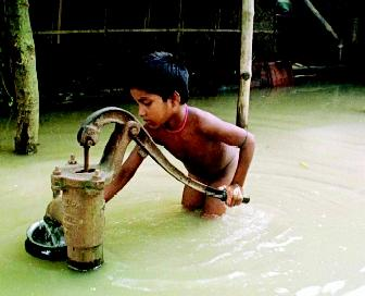 A boy in West Bengal, India pumps water from a well in a flooded area. Floodwaters can contaminate cisterns and improperly designed wells, compounding problems caused by the river currents and inundation.