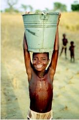 International aid programs provide safe drinking water for key localities in developing countries. Here a child in Gabisi, Ghana balances a water bucket after visiting the WaterAid pump.
