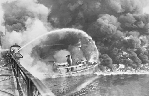 Firemen spray water on the tug Arizona as a fire sweeps the docks in Cleveland, Ohio in November 1952. The fire, which started in an oil slick on the Cuyahoga River, destroyed three tugs, three buildings, and the ship repair yards. A similar fire in June 1969 received nationwide attention and brought a sharp focus on environmental quality issues.