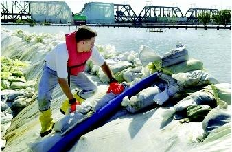 A city worker checks one of the pump hoses discharging floodwater back into the Mississippi River in Davenport, Iowa during a 2001 flood (which approached the record flood of 1993). Davenport is the largest city along the Upper Mississippi River without floodwalls, and hence relies on sandbags and other protective measures.