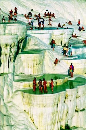 Sunbathers at Pamukkale, Turkey stand in pools atop travertine limestone terraces formed by the progressive deposition of minerals from spring waters. Highly mineralized hot water (36°C) issues from elevated springs, and flows downslope for about 100 meters. As the water cools, calcite (calcium carbonate) precipitates, forming terraces in a stair-step fashion. The natural hot springs derive from the volcanic features found in the Aegean region, and have been used since Roman times.