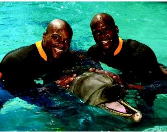 "Marine mammals are prominent residents and entertainers at aquaria and entertainment complexes throughout the world. This bottlenose dolphin ""smiles"" for the camera with its celebrity visitors, track and field athletes Calvin and Alvin Harrison."