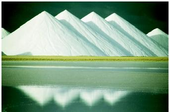 These mounds of sea salt were mined from deeply buried beds deposited when sea water evaporated in an ancient environment. The beds were preserved by being covered and then uplifted in a modern terrestrial setting. Mining accounts for most of the annual salt production, even though it also can be obtained by evaporating ocean water.