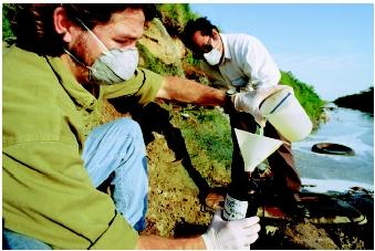 Hispanic scientists collect water samples from a canal near the U.S.-Mexico border in Texas. The canal receives industrial waste, then runs through a residential area. Water pollution is suspected of causing serious illnesses in local residents.