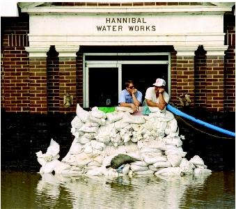 Sandbags afford only minor protection from the Mississippi River's flood waters. Buildings and infrastructure located in the floodplain (such as this water-supply pumping station in Hannibal, Missouri) are vulnerable to direct damage from flowing water, debris, and saturated soils, as well as indirect damage from contamination. For shallow unconfined aquifers, floodwaters may seep directly down to the water table.