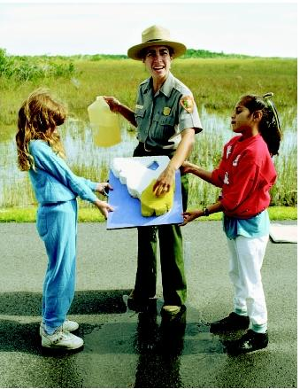 Environmental and historical education are offered by National Park Service rangers, naturalists, guides, and historians. Here a ranger involves two young visitors while explaining the Florida Everglades' water resource system.