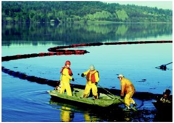 Workers clean up an oil refinery spill that polluted Anacortes Bay, Washington. The floating ring of absorbent pads trailing behind the boat is being used to contain some of the oil that has spilled.