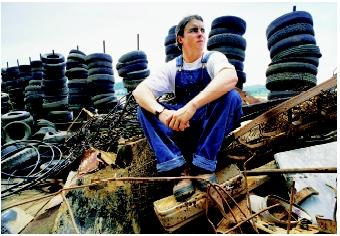"A leader of the Mississippi River Beautification and Restoration Project sits on one of the barges used to collect household trash, tires, and construction debris. River cleanup committees and various ""clean stream teams"" are ways that citizens can directly participate in environmental quality initiatives."