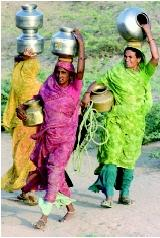 Rainwater harvesting can help improve the lives of women and children in traditional societies where the domestic water supply would otherwise require daily travel to distant wells or streams. These Indian villagers, carrying vessels of water over several kilometers, could potentially benefit from rainwater as a supplemental supply.