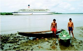 South America's Amazon River serves a range of human needs, including transportation. The contrast between the two local boys and their dugout canoes (foreground) and the cruise ship (background) exemplifies the changing and increasingly diverse demands on major world rivers.