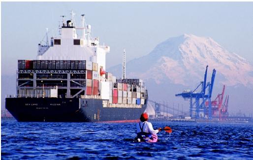 The U.S. Marine Transportation System moves people and goods via coastal and inland waterways. The diversity of the system's users is illustrated in this photograph of the Port of Tacoma, Washington, where a sea kayaker shares the water with a container vessel. (Container cranes and Mount Rainier are visible in the background.)