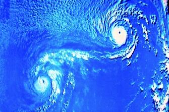 Two cyclones rotate about a point between them, illustrating the Fujiwhara effect. The two storms commonly move off together while still locked in this rotation.