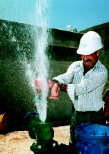 A worker reacts as water surges from a valve as a water well is activated in 1999 in Tekoa, West Bank. The well was the first to be owned and operated by the Palestinian Water Authority on the West Bank, and was financed by the U.S. Agency for International Development. The water was earmarked for the Bethlehem and Hebron areas.